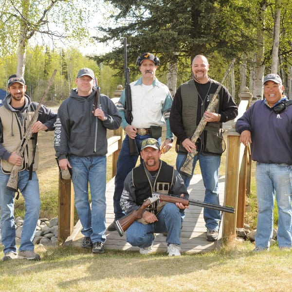 a group of men holding two barrel guns